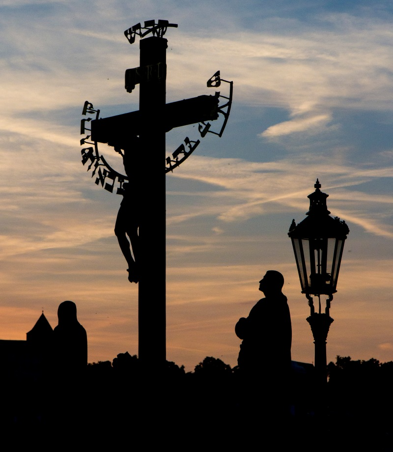 Statues on the Charles Bridge in Prague silhouetted at sunset.