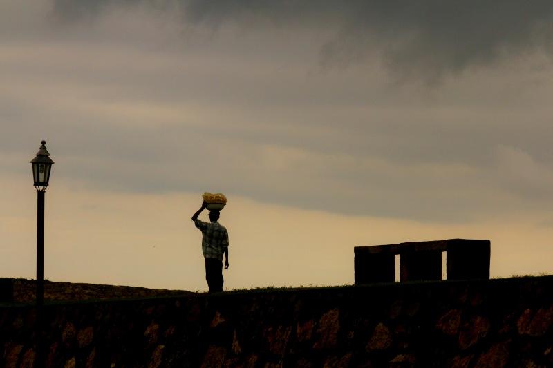 Fruit seller walking along the old walls of Galle Fort, Sri Lanka.