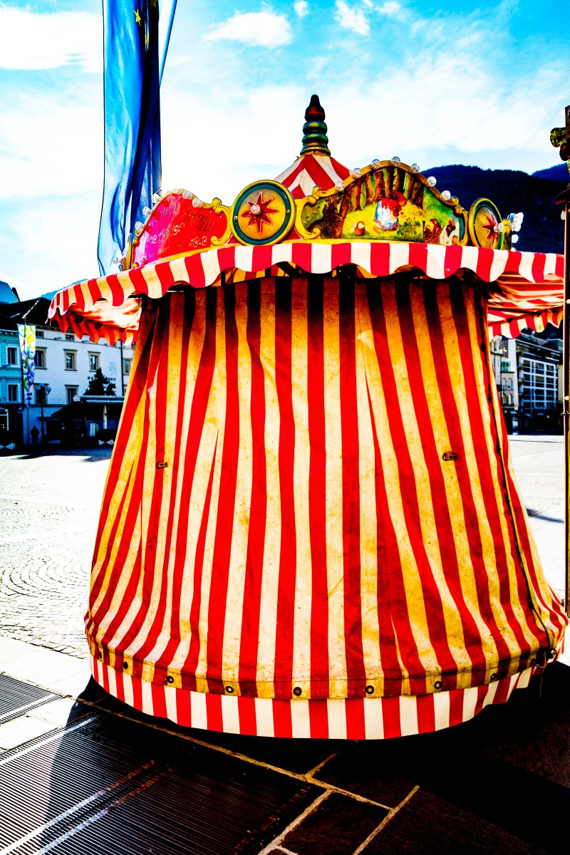 Striped tent covering miniature carousel, Walthur Piazza, Bolzano, Italy